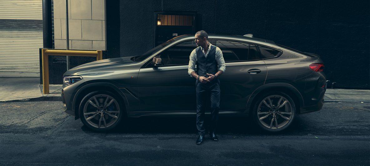 Mann lehnt an BMW X6 M50i in seitlicher Perspektive vor urbaner Kulisse