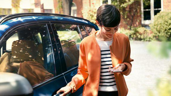 BMW Paket Care Frau mit Smartphone an der Tür ihres BMW