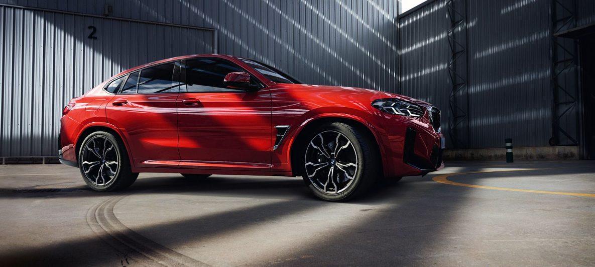 BMW X4 M F98 LCI Facelift 2021 Toronto Rot metallic Dreiviertel-Frontansicht in Fabrikhalle